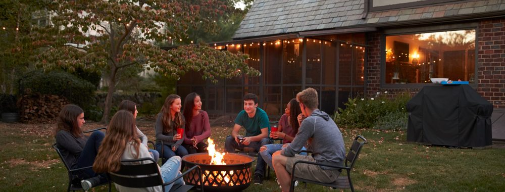 teenagers sitting around outdoor fire pit in backyard