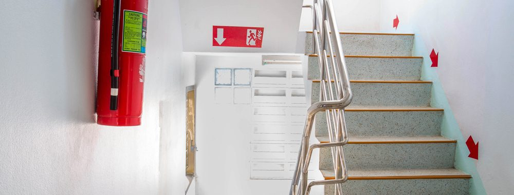 staircase in commercial building with fire exit sign and fire extinguisher