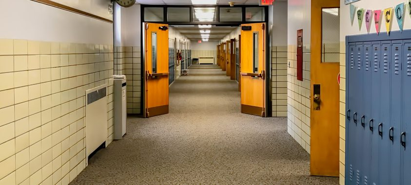 interior of school facility hallway with lockers and doorway to classrooms